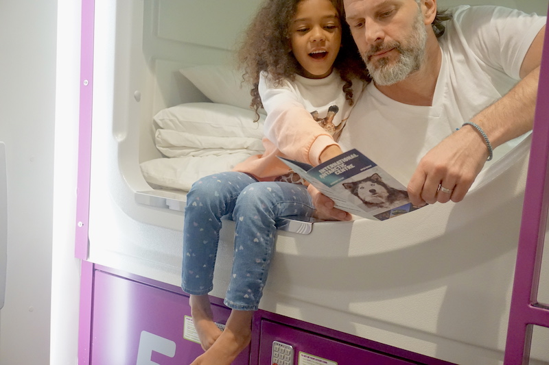 Father and daughter read together from the comfort of a Jucy pod.