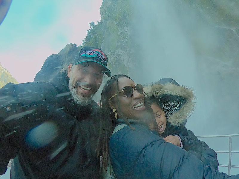 Man, woman, and child play in a waterfall on Milford Sound Jucy Cruise.
